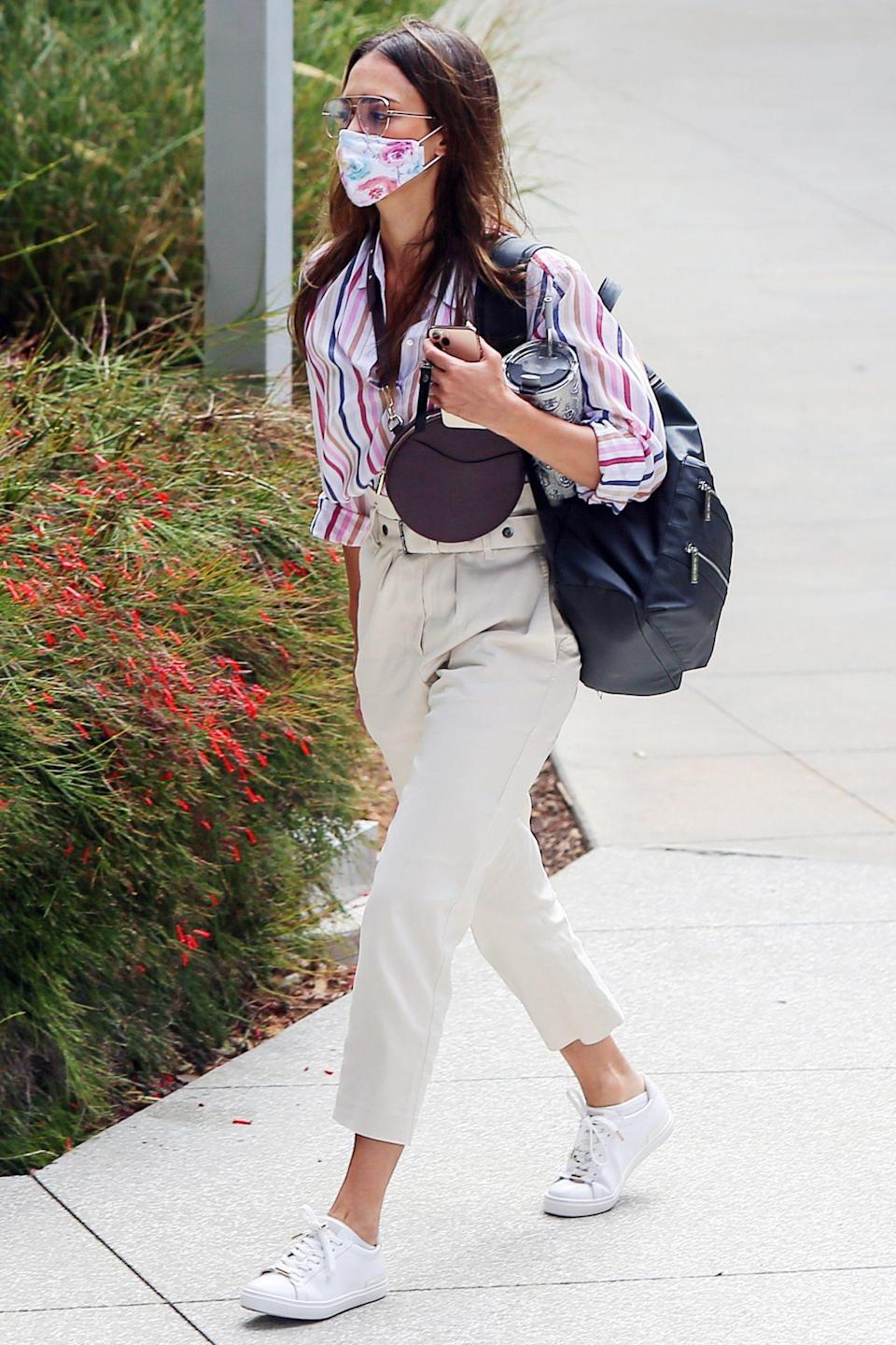 <p>A colorful, masked Jessica Alba makes her way to The Honest Company offices in Los Angeles on Tuesday.</p>