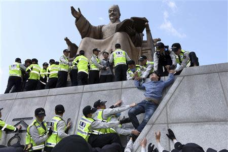 Policemen detain university students on a statue of King Sejong the Great during a protest against South Korean President Park Geun-hye, in central Seoul May 8, 2014. REUTERS/Han Jae-ho