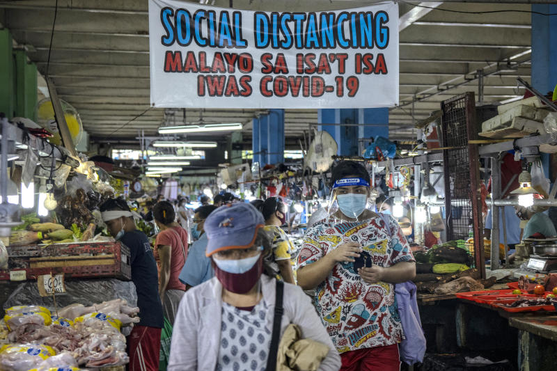 FILE PHOTO: Filipinos are seen wearing face masks and face shields inside a wet market on August 19, 2020 in Quezon City, Philippines. (Photo by Ezra Acayan/Getty Images)