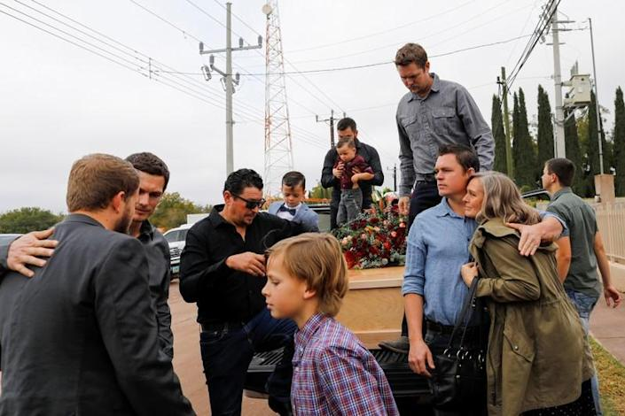 Relatives of Christina Marie Langford Johnson, who was killed by unknown assailants, stand next to her coffin during the funeral service before a burial at the cemetery in LeBaron, Chihuahua