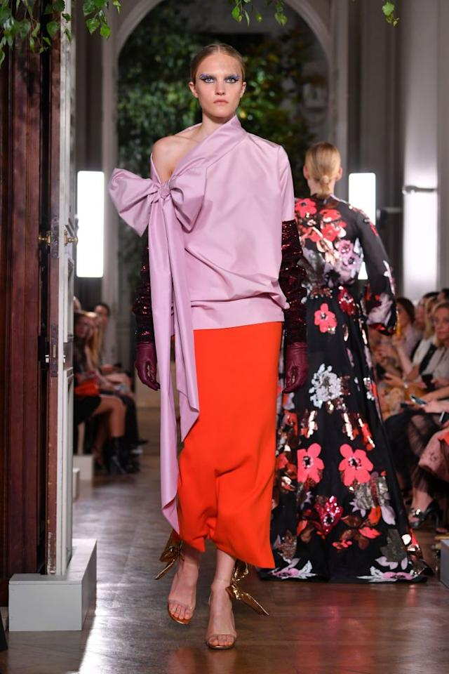 <p>This one shoulder top from Valentino's latest collection, complete with a dangling bow, was paired with a crimson skirt on the runway.</p>