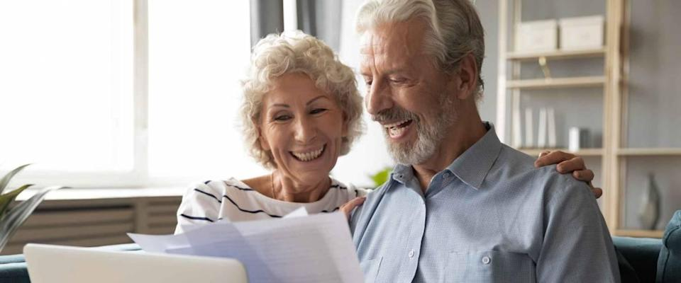 Cheerful elderly couple sit on couch, smiling and looking at bills