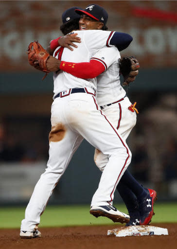 Atlanta Braves second baseman Ozzie Albies, right, and shortstop Dansby Swanson embrace after the team's 8-1 win in a baseball game against the Miami Marlins on Saturday, May 19, 2018, in Atlanta. (AP Photo/John Bazemore)