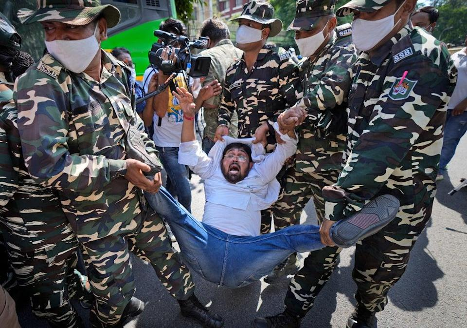 Paramilitary force soldiers detain an activist of Congress party's youth wing protesting against Sunday's killing of four farmers in Uttar Pradesh state after being run over by a car  (AP)