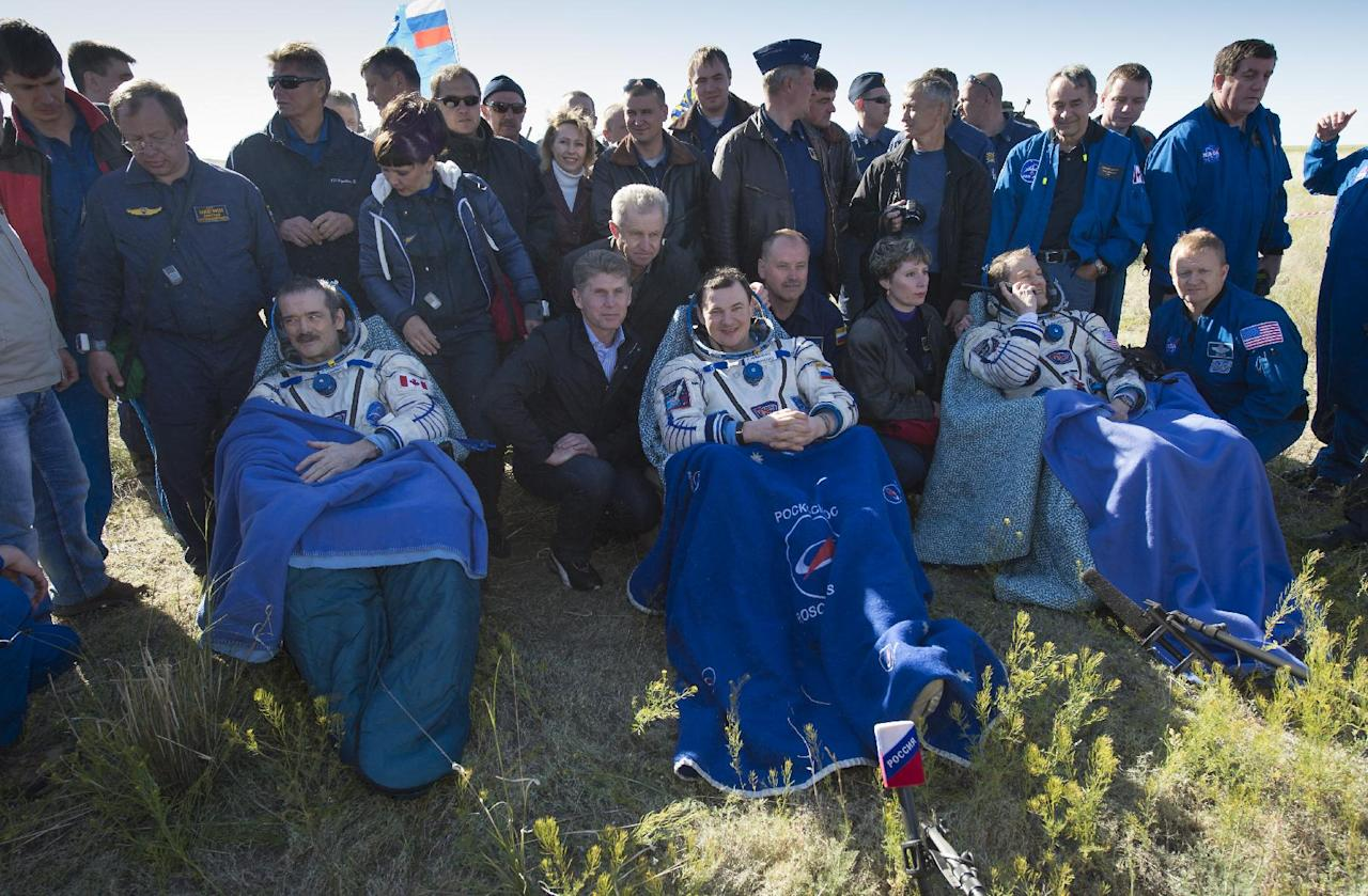 In this image provided by NASA Expedition 35 Commander Chris Hadfield of the Canadian Space Agency, left, Russian Flight Engineer Roman Romanenko of the Russian Federal Space Agency, center, and NASA Flight Engineer Tom Marshburn sit in chairs outside the Soyuz Capsule just minutes after they landed in a remote area outside the town of Dzhezkazgan, Kazakhstan, on Tuesday morning, May 14, 2013. Hadfield, Romanenko and Marshburn are returning from five months onboard the International Space Station where they served as members of the Expedition 34 and 35 crews. (AP Photo/NASA, Carla Cioffi)