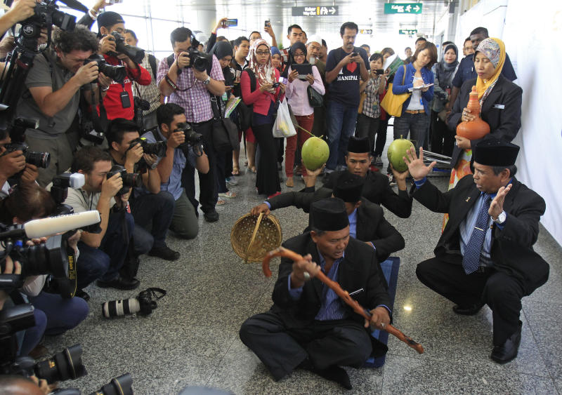FILE - In this March 12, 2014 file photo, well-known Malaysian shaman Ibrahim Mat Zin, bottom right, uses spiritual methods and prayers to locate the missing Malaysia Airlines plane MH370 at Kuala Lumpur International Airport in Sepang, Malaysia. Solving the mystery of the missing Malaysian plane is proving to be as easy as cracking a homicide without a body, witness or motive. All while billions of people are waiting for the kind of quick and clear resolution that we've come to expect in the information age _ and speculating in sometimes wild ways when that resolution doesn't come. (AP Photo/Lai Seng Sin, File)