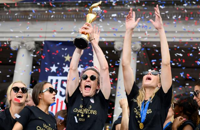 """USA women's soccer player Megan Rapinoe (C) and other team members celebrate with the trophy in front of the City Hall after the ticker tape parade for the women's World Cup champions on July 10, 2019 in New York. - Tens of thousands of fans are poised to pack the streets of New York on Wednesday to salute the World Cup-winning US women's team in a ticker-tape parade. Four years after roaring fans lined the route of Lower Manhattan's fabled """"Canyon of Heroes"""" to cheer the US women winning the 2015 World Cup, the Big Apple is poised for another raucous celebration. (Photo by Johannes Eisele/AFP/Getty Images)"""