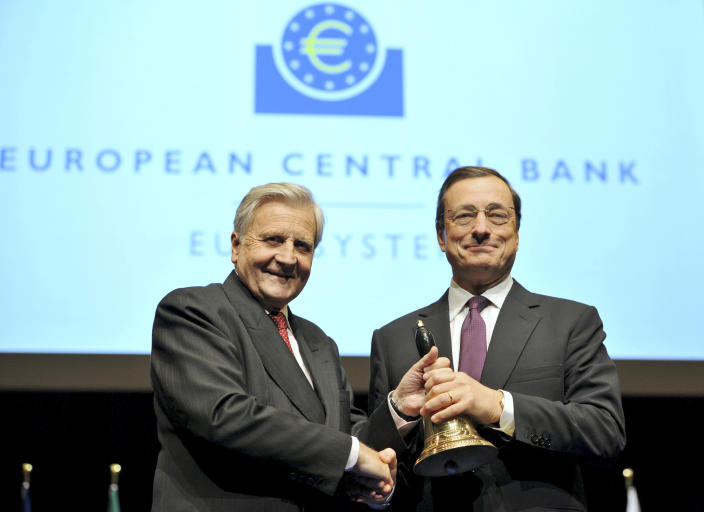 FILE - In this Oct. 19, 2011 file photo outgoing European Central Bank (ECB) President Jean-Claude Trichet, left, hands over a bell to his successor Mario Draghi from Italy at the end of a farewell ceremony at the old opera house in Frankfurt, Germany. Draghi officially takes over as head of the ECB on Tuesday, Nov. 1, 2011, in a high-pressure struggle with eurozone government leaders over how far the bank should go in rescuing indebted governments. (AP Photo/Arne Dedert, pool)