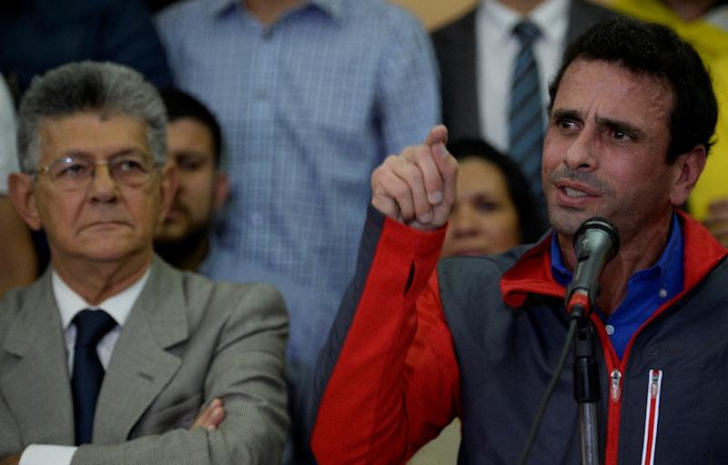 Venezuelan opposition leader Henrique Capriles speaks next to the president of the National Assembly, Henry Ramos Allup, during a press conference in Caracas on October 21, 2016 (AFP Photo/Federico Parra)