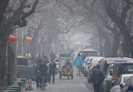 FILE PHOTO: People are seen in a traditional alleyway on a polluted day in central Beijing