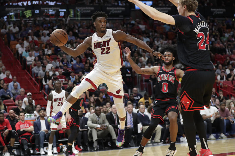 Miami Heat forward Jimmy Butler (22) passes as Chicago Bulls guard Coby White (0) and forward Lauri Markkanen (24) defend during the second half of an NBA basketball game, Sunday, Dec. 8, 2019, in Miami. The Heat won 110-105 in overtime. (AP Photo/Lynne Sladky)