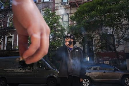 sTwenty-one year old men smoke outside a friend's apartment in Lower Manhattan, New York