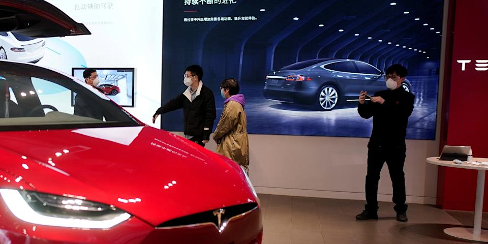 FILE PHOTO: People wearing face masks are seen inside a Tesla showroom at a shopping mall in Wuhan, Hubei province, the epicentre of China's coronavirus disease (COVID-19) outbreak, March 30, 2020. REUTERS/Aly Song