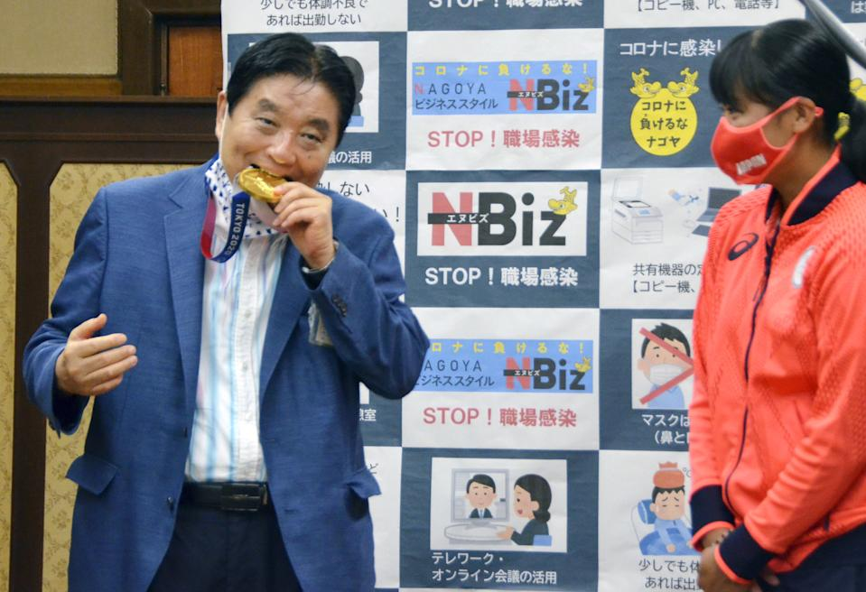 Nagoya city Mayor Takashi Kawamura bites the Tokyo 2020 Olympic Games gold medal of the softball athlete Miu Goto during a ceremony in Nagoya, central Japan, August 4, 2021, in this photo taken by Kyodo. Picture taken August 4, 2021. Mandatory credit Kyodo/via REUTERS   ATTENTION EDITORS - THIS IMAGE WAS PROVIDED BY A THIRD PARTY. MANDATORY CREDIT. JAPAN OUT. NO COMMERCIAL OR EDITORIAL SALES IN JAPAN.