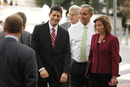 U.S. Representative Ryan smiles and talks with fellow House Republicans at the Republican National Committee offices in Washington