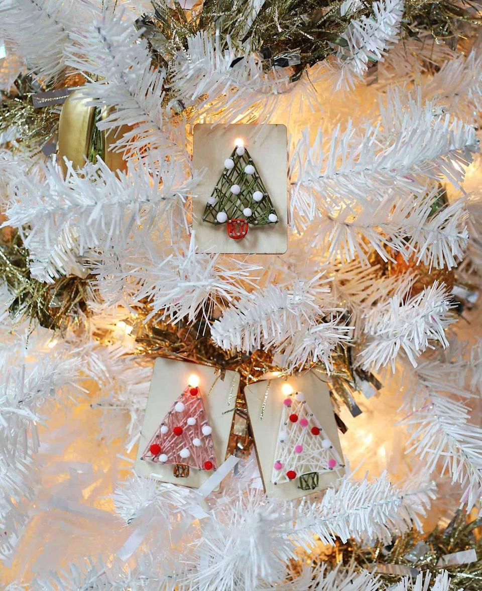 """<p>Drive a few nails into a piece of wood, then get creative with some string and pom-poms to turn scraps into treasure. </p><p><em>Get the tutorial at <a href=""""https://abeautifulmess.com/diy-string-art-ornaments/"""" rel=""""nofollow noopener"""" target=""""_blank"""" data-ylk=""""slk:A Beautiful Mess"""" class=""""link rapid-noclick-resp"""">A Beautiful Mess</a>.</em></p><p><a class=""""link rapid-noclick-resp"""" href=""""https://www.amazon.com/Lily-Variety-Assortment-Holiday-Multicolor/dp/B075ZJ3WZF?tag=syn-yahoo-20&ascsubtag=%5Bartid%7C10072.g.34443405%5Bsrc%7Cyahoo-us"""" rel=""""nofollow noopener"""" target=""""_blank"""" data-ylk=""""slk:SHOP HOLIDAY YARN"""">SHOP HOLIDAY YARN</a></p>"""