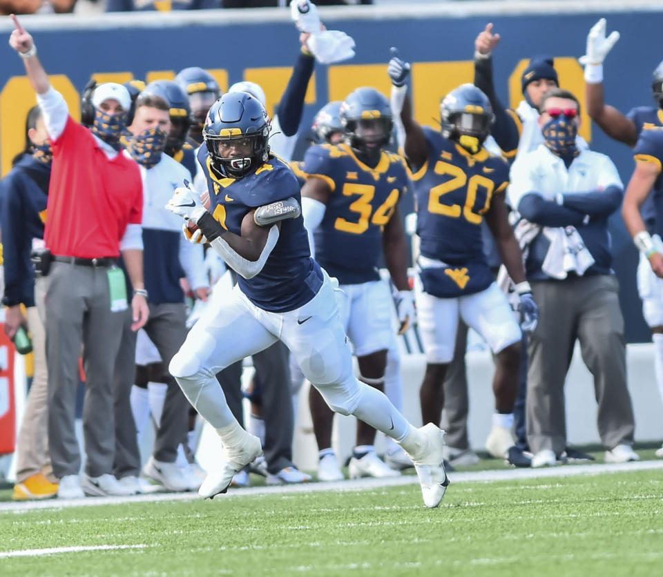 West Virginia running back Leddie Brown (4) rushes the ball against TCU during the second half of an NCAA college football game on Saturday, Nov. 14, 2020, in Morgantown, W.Va. (William Wotring/The Dominion-Post via AP)