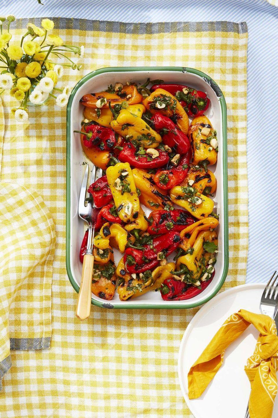 """<p>Grilled baby peppers get topped with a savory and tangy cilantro cashew sauce. </p><p><strong><a href=""""https://www.countryliving.com/food-drinks/a32353796/charred-baby-peppers-with-lime-and-cashew-vinaigrette/"""" rel=""""nofollow noopener"""" target=""""_blank"""" data-ylk=""""slk:Get the recipe"""" class=""""link rapid-noclick-resp"""">Get the recipe</a>.</strong></p>"""