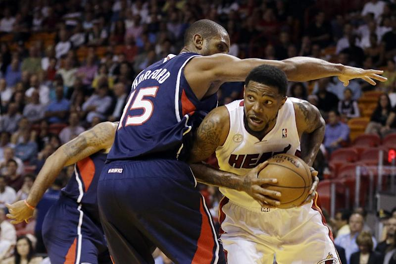 Atlanta Hawks' Al Horford (15) pressures Miami Heat's Udonis Haslem (40) during the first half of an NBA basketball game in Miami, Tuesday, March 12, 2013. (AP Photo/J Pat Carter)