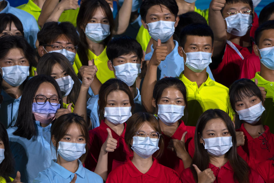 """Participants wearing face masks pose for a group photo after a launch ceremony to reveal the motto for the 2022 Beijing Winter Olympics and Paralympics in Beijing, Friday, Sept. 17, 2021. Organizers on Friday announced """"Together for a Shared Future"""" as the motto of the next Olympics, which is scheduled to begin on Feb. 4 of next year. (AP Photo/Mark Schiefelbein)"""