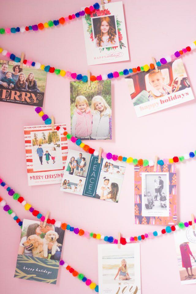 """<p>For a fun and clever way to display all of those Christmas cards that arrive on your doorstep, craft this pom-pom garland. Prefer a more traditional color scheme? Just use red and white pom-poms instead. </p><p><a href=""""https://designimprovised.com/2016/12/pom-pom-garland-christmas-card-display-idea.html"""" rel=""""nofollow noopener"""" target=""""_blank"""" data-ylk=""""slk:Get the tutorial."""" class=""""link rapid-noclick-resp"""">Get the tutorial.</a></p><p><a class=""""link rapid-noclick-resp"""" href=""""https://www.amazon.com/JABINCO-Pack-Wooden-Clothespins-About/dp/B0852TXHZG/?tag=syn-yahoo-20&ascsubtag=%5Bartid%7C10072.g.37499128%5Bsrc%7Cyahoo-us"""" rel=""""nofollow noopener"""" target=""""_blank"""" data-ylk=""""slk:SHOP CLOTHESPINS"""">SHOP CLOTHESPINS</a></p>"""