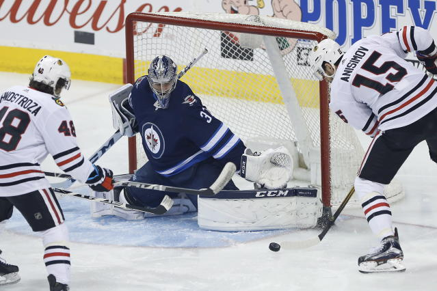 Chicago Blackhawks center Artem Anisimov (15) misses on a shot against Winnipeg Jets goaltender Connor Hellebuyck (37) during the first period of an NHL hockey game Thursday, March 15, 2018, in Winnipeg, Manitoba. (John Woods/The Canadian Press via AP)