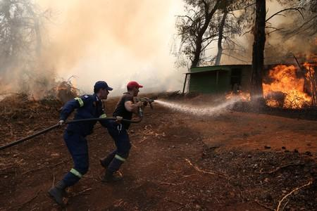 Firefighters try to extinguish a wildfire burning in village of Makrimalli on the island of Evia
