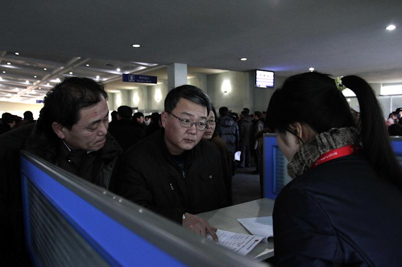 FILE - In this Tuesday, Jan. 22, 2013 photo, foreigners speak with sales person at a Koryolink cellphone rental booth, asking about mobile phone service at Pyongyang Airport in Pyongyang, North Korea.  Koryolink informed foreign residents in Pyongyang on Friday, Feb. 22, 2013,  that it will launch a high-speed 3G Internet service, taking another step toward interconnectivity by allowing foreigners to tweet, Skype and surf the Internet from their cellphones, iPads and laptops. North Korean citizens will not have access to the new 3G mobile Internet service. (AP Photo/Jon Chol Jin, File)