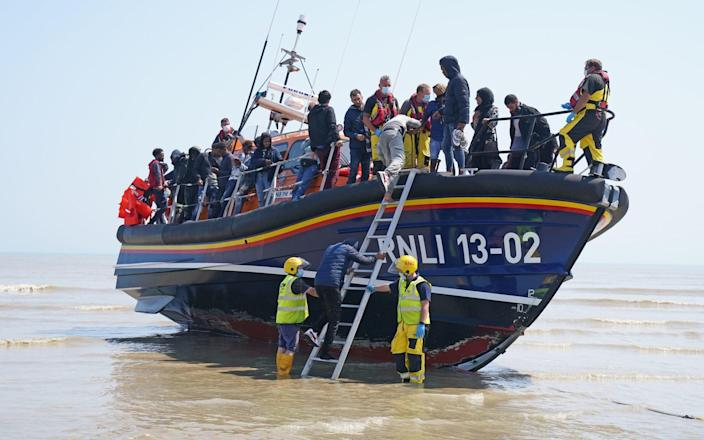 A group of people thought to be migrants crossing from France come ashore from the local lifeboat at Dungeness in Kent, after being picked up from a small boat in the Channel - Gareth Fuller/PA