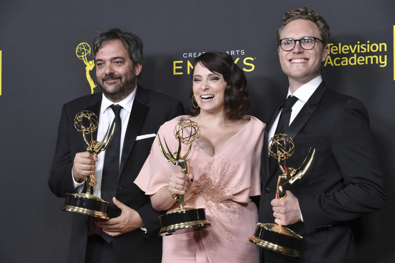 """FILE - This Sept. 14, 2019 file photo shows Adam Schlesinger, from left, Rachel Bloom and Jack Dolgen in the press room with the awards for outstanding original music and lyrics for """"Crazy Ex Girlfriend"""" at the Creative Arts Emmy Awards in Los Angeles. Schlesinger, an Emmy and Grammy winning musician and songwriter known for his band Fountains of Wayne and his songwriting on the TV show """"Crazy Ex-Girlfriend,"""" has died from coronavirus at age 51. (Photo by Richard Shotwell/Invision/AP, File)"""