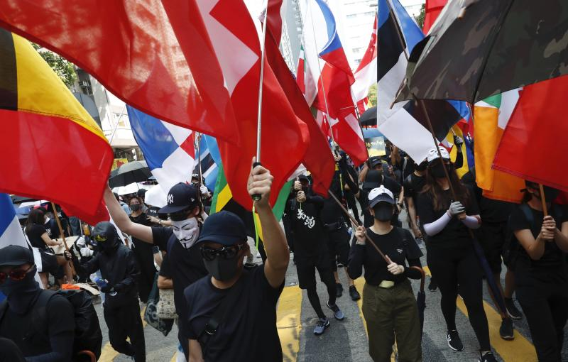 """Anti-government protesters march past police headquarters in Hong Kong, Tuesday, Oct. 1, 2019. Thousands of black-clad pro-democracy protesters defied a police ban and marched in central Hong Kong on Tuesday, urging China's Communist Party to """"return power to the people"""" as the party celebrated its 70th year of rule. (AP Photo/Gemunu Amarasinghe )"""
