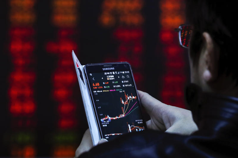 An investor checks stock prices through his smartphone at a brokerage house in Beijing, Friday, Dec. 20, 2019. Stocks were mixed in early trading in Asia on Friday after Wall Street posted more record highs, extending the market's gains for the week. (AP Photo/Andy Wong)
