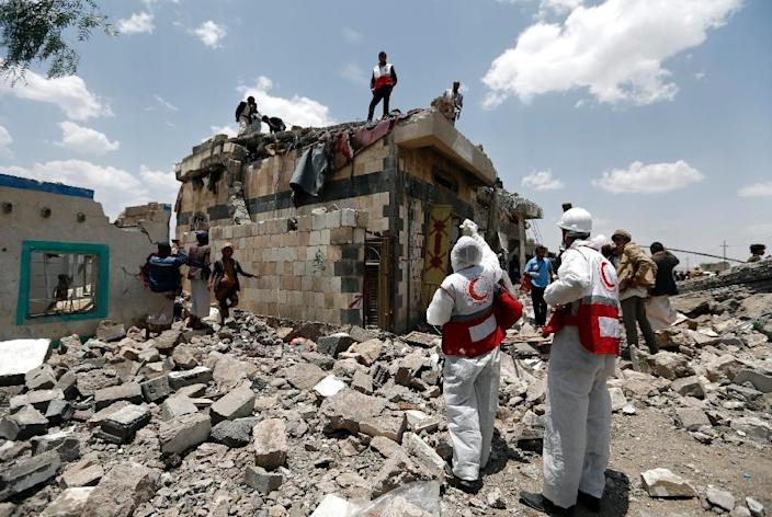 Yemeni Red Crescent workers and civilians stand at the site of an air raid in the Arhab area on the outskirts of Sanaa, on August 23, 2017 (AFP Photo/Mohammed HUWAIS)