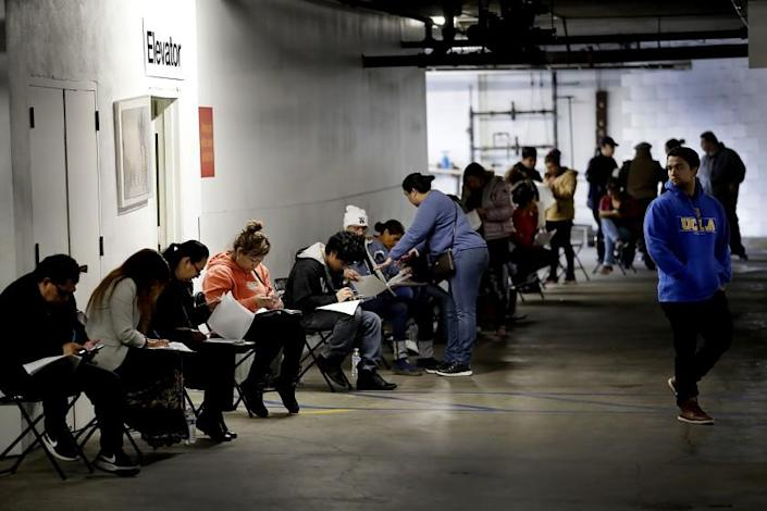 CALIFORNIA: March 13, 2020, unionized hospitality workers wait in line in a basement garage to apply for unemployment benefits at the Hospitality Training Academy in Los Angeles. More than 6.6 million Americans applied for unemployment benefits last week, far exceeding a record high set just last week, a sign that layoffs are accelerating in the midst of the coronavirus.
