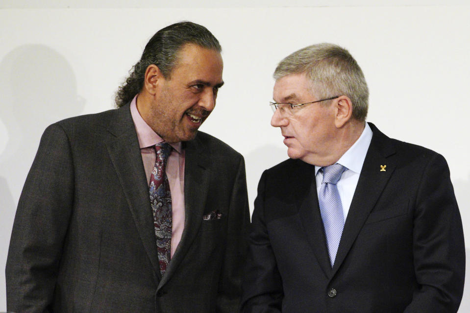 FILE - In this Wednesday, Nov. 28, 2018 file photo, Sheikh Ahmad al Fahad al Sabah, left, president of the Association of National Olympic Committees (ANOC), and IOC President Thomas Bach talk prior to the opening of the ANOC general assembly in Tokyo. Olympic powerbroker Sheikh Ahmad al-Fahad al-Sabah will go on trial in Switzerland this month accused of forgery in a case linked to political rivalry in Kuwait's royal family. Lawyers for the sheikh say he will attend the hearing listed by a criminal court in Geneva to run from Feb. 22-26, 2021. (AP Photo/Eugene Hoshiko, fle)
