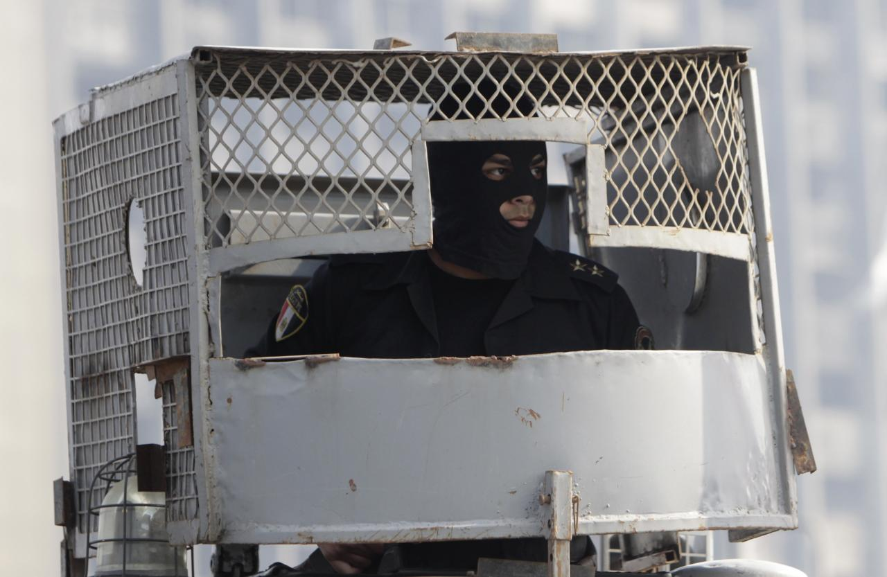 A riot policeman sits inside a police vehicle on October bridge during clashes with anti-government protesters and members of the Muslim Brotherhood, near Tahrir Square in downtown Cairo, on the third anniversary of Egypt's uprising, January 25, 2014. Twenty-nine people were killed during anti-government marches on Saturday while thousands rallied in support of the army-led authorities, underlining Egypt's volatile political fissures three years after the fall of autocrat President Hosni Mubarak. Security forces lobbed teargas and some fired automatic weapons in the air to try to prevent demonstrators opposed to the government reaching Tahrir Square, the symbolic heart of the 2011 uprising that toppled the former air force commander. REUTERS/Mohamed Abd El Ghany (EGYPT - Tags: POLITICS CIVIL UNREST TPX IMAGES OF THE DAY ANNIVERSARY CRIME LAW)