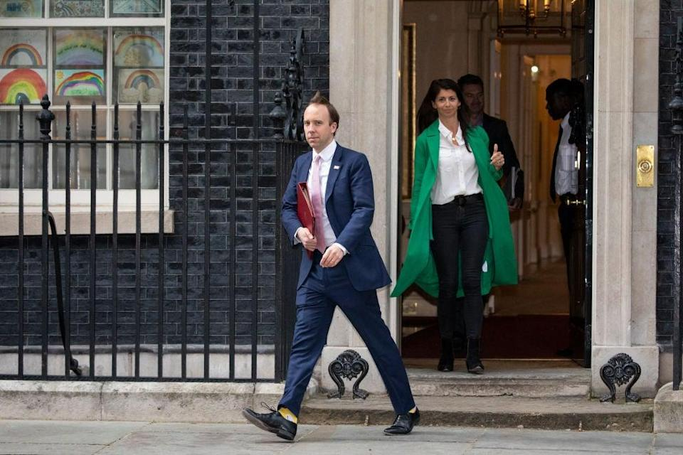 Matt Hancock leaves 10 Downing Street after the daily press briefing in May, with Gina Colandangelo in the green coat (Getty Images)