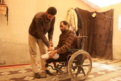 Ali's younger brother helps him get around in the wheel chair he has used since he lost his legs to a landmine explosion