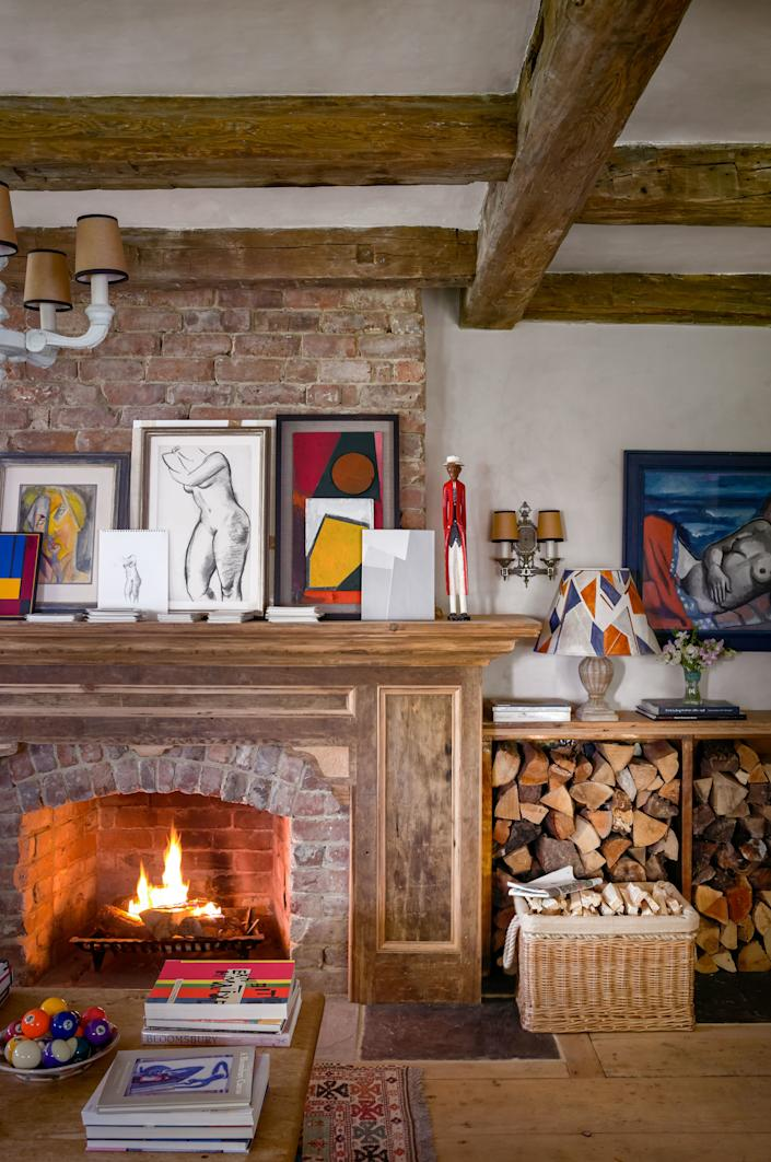 """<div class=""""caption""""> In the living room, artworks by McNally, his son George and his friends, and André Lhote (left) and Bernard Meninsky (large nude study), top the custom mantel. Vintage sconce; 1932 painting (on wall) by Hermann Max Pechstein. </div>"""