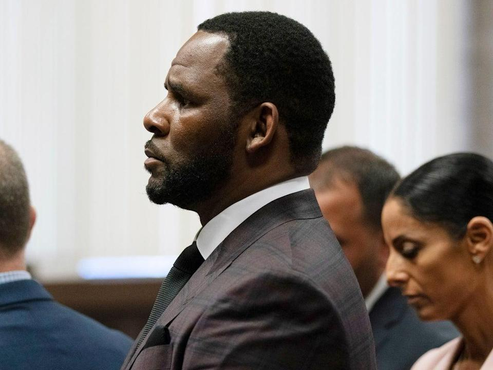 R Kelly (centre) appears at a court hearing on 26 June 2019 in Chicago, Illinois (E Jason Wambsgans-Pool/Getty Images)