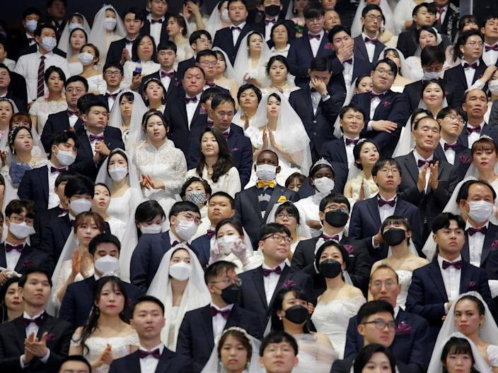 Couples wearing masks for protection from the new coronavirus, attend a mass wedding ceremony of the Unification Church at Cheongshim Peace World Centre in Gapyeong, South Korea, February 7, 2020. REUTERS/Heo Ran