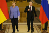 Russian President Vladimir Putin, right, and German Chancellor Angela Merkel enter the hall for a joint news conference following their talks in the Kremlin in Moscow, Russia, Friday, Aug. 20, 2021. The talks between Merkel and Putin are expected to focus on Afghanistan, the Ukrainian crisis and the situation in Belarus among other issues. (AP Photo/Alexander Zemlianichenko, Pool)