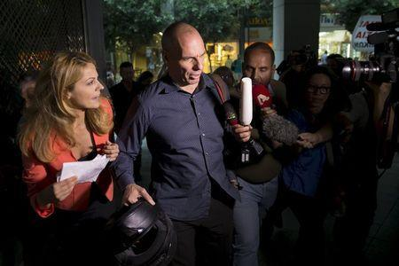 Greek Finance Minister Yanis Varoufakis surrounded by the media as he leaves Finance Ministry building in Athens, Greece, July 1, 2015. REUTERS/Marko Djurica