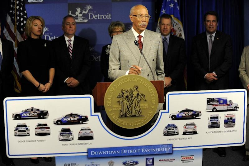 """Detroit Mayor Dave Bing, center, unveils an ambitious plan by local business leaders to fund the purchase of public safety vehicles for the cash-strapped city, on Monday, March 25, 2013. In what was described as an """"unprecedented collaboration,"""" Bing held a press conference with industrialist Roger Penske to announce the plan that included an $8 million donation for the leasing of 23 new EMS vehicles and 100 police cruisers. A separate $6 million has also been committed for recreation programming in the city, with $5 million from Lear Corp. and $1 million from DTE Energy Co. (AP Photo/The  Detroit News, David Coates)"""