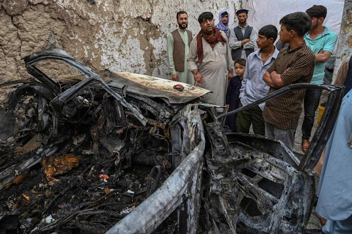 Afghan residents and family members of the victims gather next to a damaged vehicle inside a house, day after a US drone airstrike in Kabul on 30 August, 2021.  ((Photo by WAKIL KOHSAR / AFP))