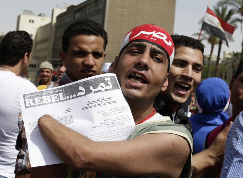 """FILE - In this Friday, May 17, 2013 file photo, An Egyptian protester shouts anti-President Mohammed Morsi slogans as he holds an application for """"Tamarod"""", Arabic for """"rebel"""", a campaign calling for the ouster of Egyptian President Mohammed Morsi and for early presidential elections, during a protest in Tahrir Square, in Cairo, Egypt. Opponents of Egypt's Islamist president are convinced that nationwide protests planned for June 30 are their last opportunity to drive him from power. They say they have tapped into widespread public discontent over shortages, broken infrastructure, high prices and lack of security, and can bring that anger into the streets. (AP Photo/Hassan Ammar, File)"""