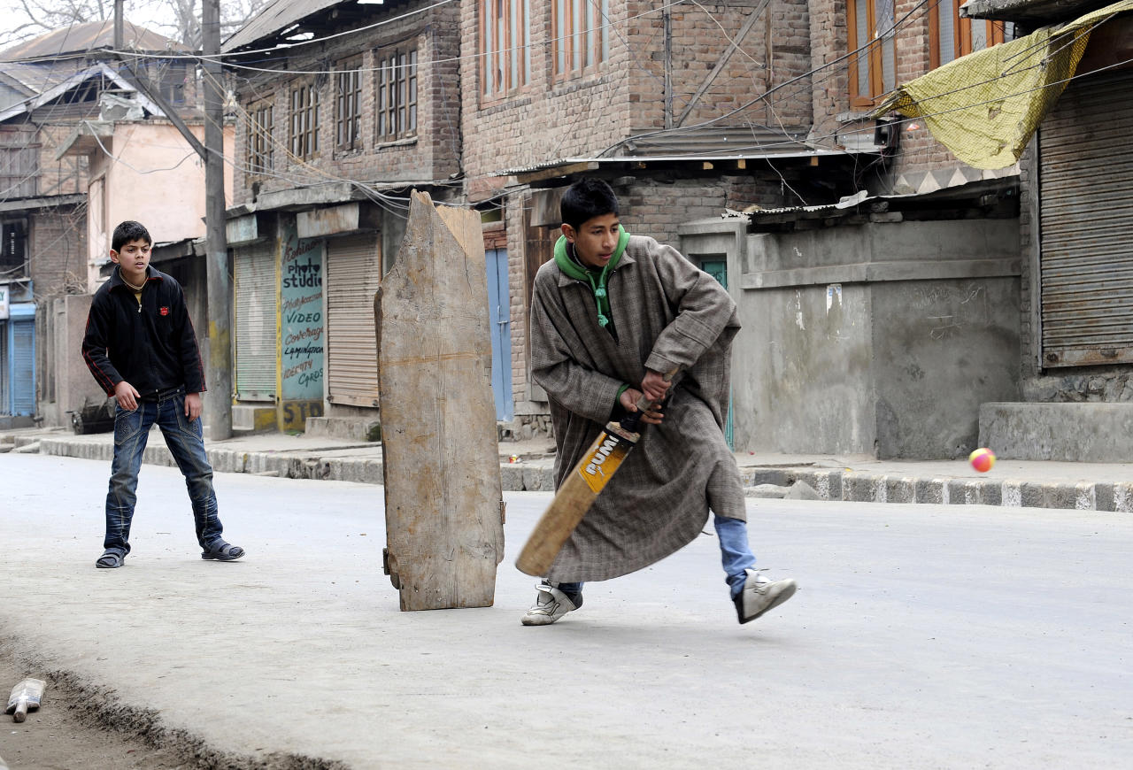 Indian Kashmiri youths play cricket on a deserted street during a strike in Srinagar on February 22, 2011.  The All Parties Hurriyat (Freedom) Conference Kashmir's main separatist alliance, called for the one-day strike aganist Indian Police action to restrict the movement of Kashmiri hardline leader Syed Ali Shah Geelani.  Geelani, who led the massive anti-India protests in Muslim majority Kashmir last year, was asked by Indian police not to leave Delhi where he had gone for medical check-up last month. AFP PHOTO/Rouf BHAT (Photo credit should read ROUF BHAT/AFP/Getty Images)