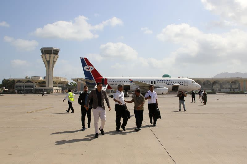 Crew members of the Yemen Airways plane that carried members of Yemen's newly-formed government walk on the tarmac after explosions hit the airport in Aden