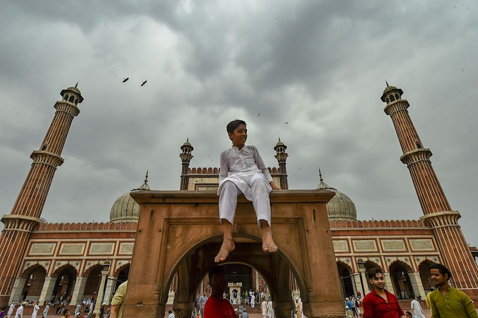 New Delhi: A Muslim boy sits on an arch at Jama Masjid in New Delhi on Friday, 16 April, during the ongoing holy month of 'Ramzan'.
