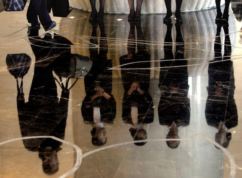 File photo of a porter carrying luggage past a group of reception staff that are reflected in the floor as they stand in the foyer of the five-star rated Sofitel Hotel in Beijing